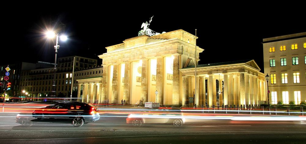 Traffic at night passing by the Brandenburg Gate in Berlin, Germany